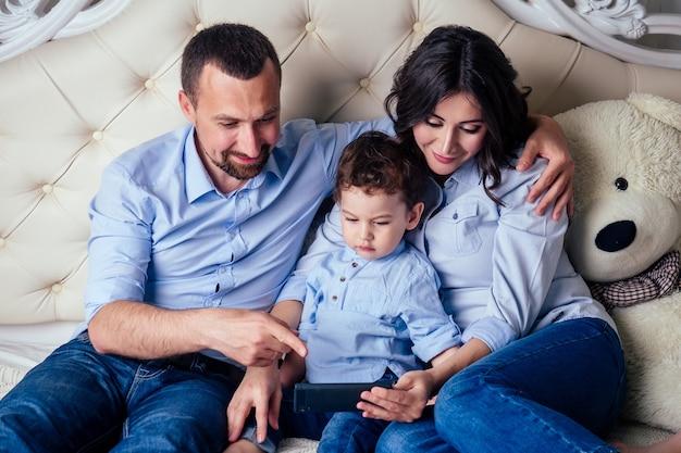Gelukkig gezin, mooie moeder, zoontje en vader lezen samen een sprookje online in de telefoon op bed in de slaapkamer