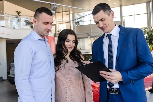 Gelukkig gezin ondertekening contract met dealer in salon