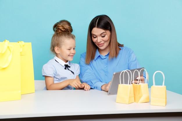 Gelukkig gezin online winkelen concept. moeder en kind chooding dingen op internet geïsoleerd.