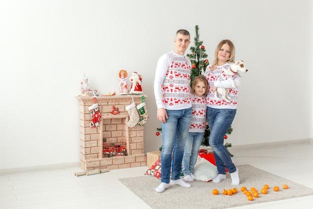 Gelukkig gezin. ouders en kind bij kerstboom thuis