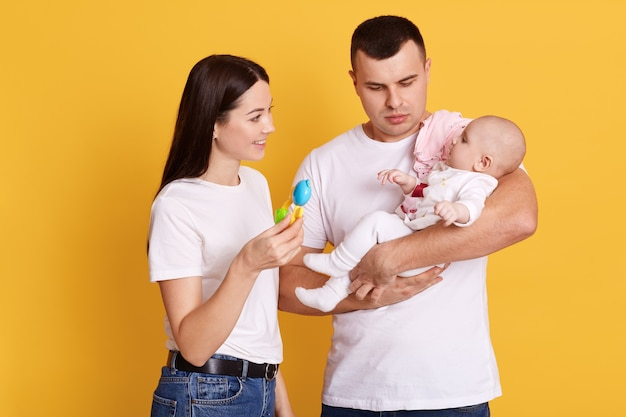 Gelukkig gezin spelen met hun pasgeboren dochter terwijl poseren geïsoleerd over gele muur
