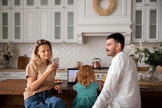Gelukkig gezin thuis met medium shot van apparaten