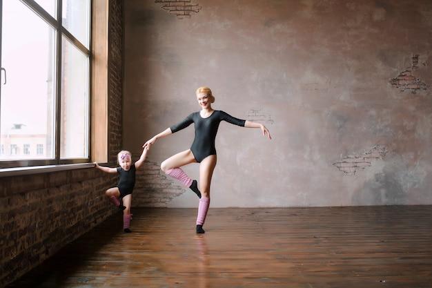 Gelukkig gezin, twee ballerina's, moeder en dochter in zwarte turnpakjes tegen de roze muur