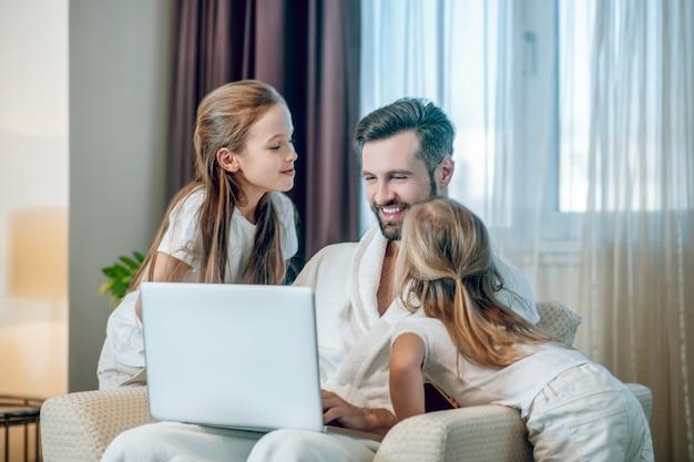 Gelukkig gezin. twee meisjes die hun liefde aan papa tonen en er gelukkig uitzien
