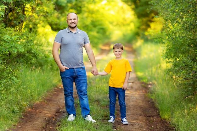 Gelukkig gezin: vader en zoon lopen hand in hand buiten in de zomer
