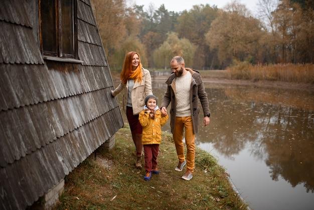 Gelukkig gezin. vader, moeder en zoon die pret hebben en op de herfstaard spelen.