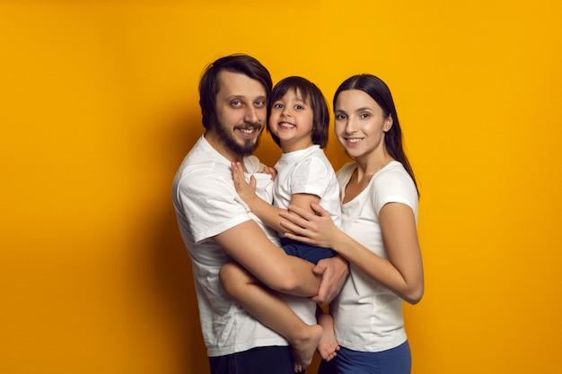 Gelukkig gezin van drie een jongen en een kind in witte t-shirts staan op een gele muur