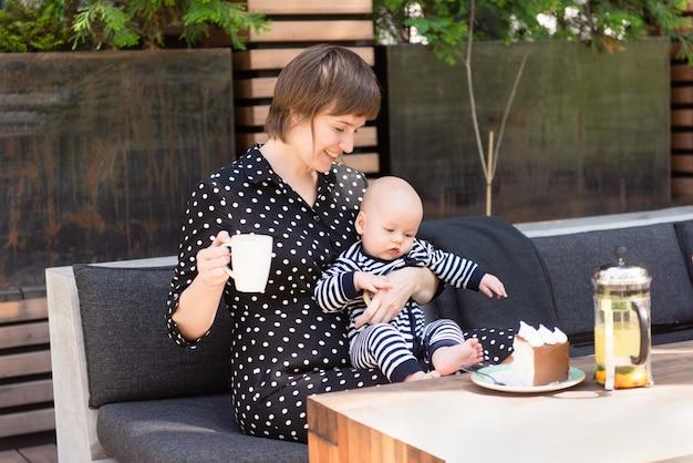 Gelukkig gezin van twee, jonge vrouw met haar schattige peuter zoon, samen ontspannen in de zomer buiten café moeder en kind, ouderschap concept