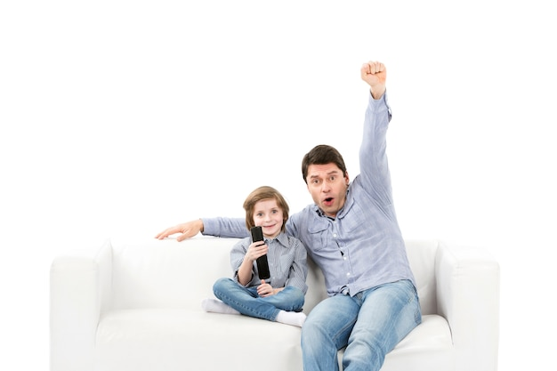 Gelukkig gezin van twee personen, vader en zoon fans op de bank met een afstandsbediening van tv