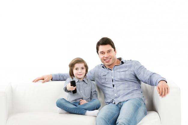Gelukkig gezin van twee personen, vader en zoon op de bank met een afstandsbediening van tv