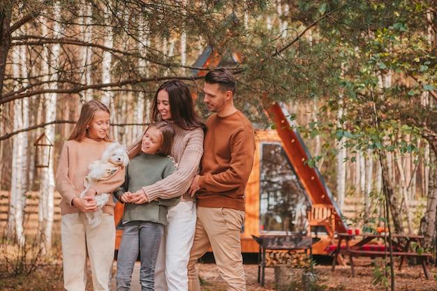 Gelukkig gezin van vier genieten op de achtergrond van de herfstdag van hun huis