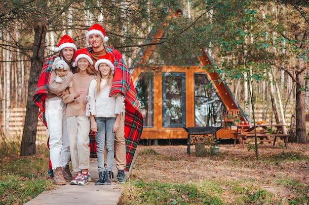Gelukkig gezin van vier in kerstman hoed genieten van kerstvakantie. ouder met kinderen gewikkeld in een deken