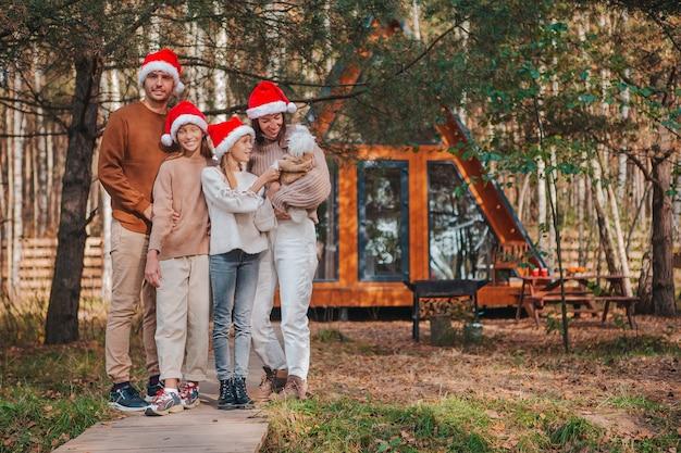 Gelukkig gezin van vier in kerstmuts genieten van kerstvakantie van hun huis