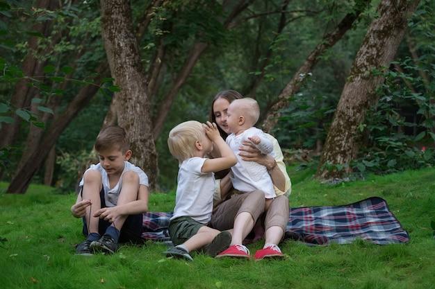 Gelukkig gezin van vier met picknick in het park. moeder en drie kinderen zitten op picknickdeken. weekend buiten
