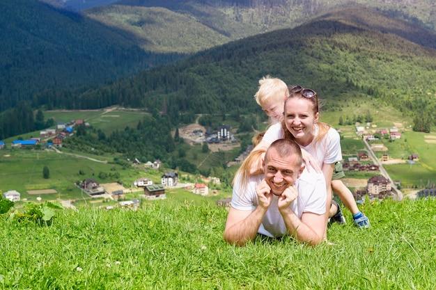 Gelukkig gezin. vrolijke vader, moeder en twee zonen liggen op het groene gras tegen de achtergrond van het bos, de bergen en de hemel met wolken.