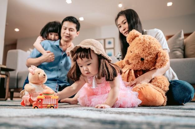 Gelukkig gezinouders spelen met teddyberen en speelgoed terwijl hun kinderen op het tapijt zitten