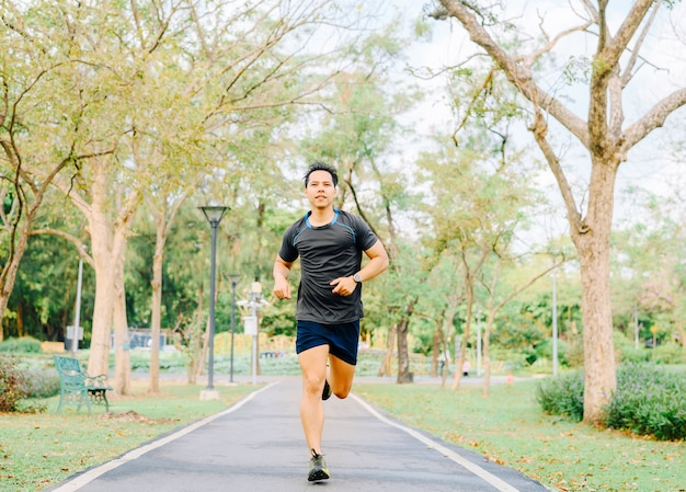 Gelukkig gezonde aziatische man loper buiten uitgevoerd in het park in de ochtend