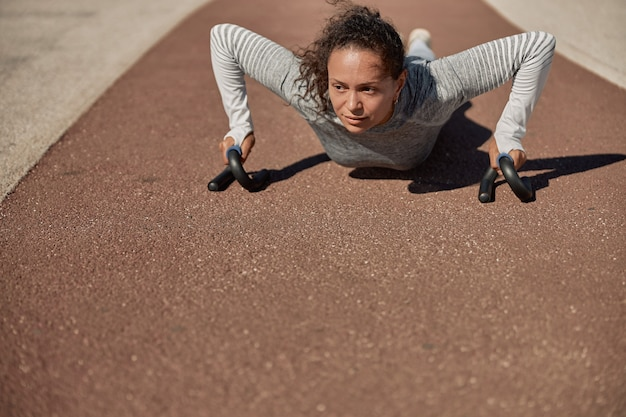 Gelukkig gezonde en sportieve vrouw doet push-up trainingen in zonnige dag