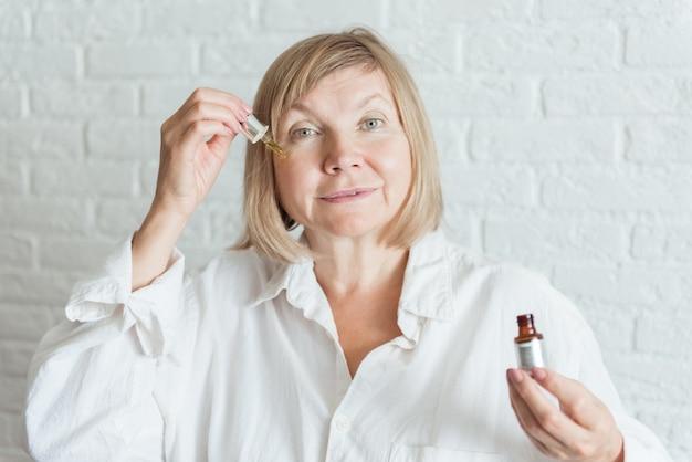 Gelukkig gezonde oude senior rijpe vrouw met gezicht huidverzorging cosmetische vloeibare serum fles in de hand thuis, volwassen middelbare leeftijd anti leeftijd rimpel natuurlijke schoonheid huidverzorging behandeling concept, close-up