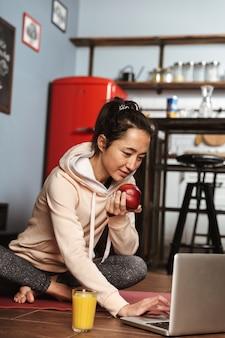 Gelukkig gezonde vrouw zittend op een fitness-mat en met behulp van laptop na yoga thuis oefenen