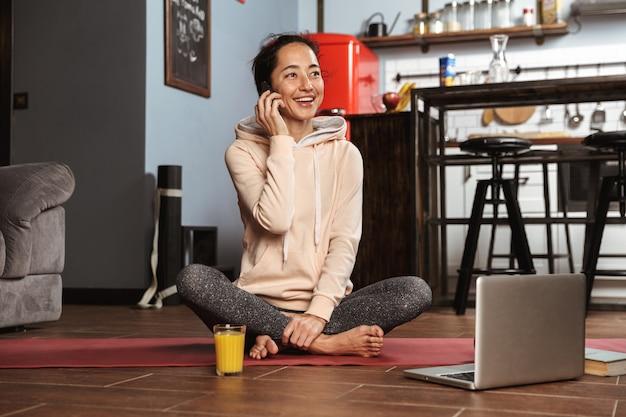 Gelukkig gezonde vrouw zittend op een fitness-mat en thuis praten over de mobiele telefoon