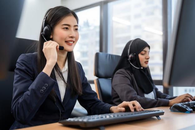 Gelukkig glimlachend aziatisch vrouwencall centre en exploitant die hoofdtelefoons dragen die aan computer werken en met klant met haar de dienstmening spreken