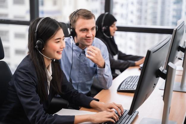 Gelukkig glimlachend aziatisch vrouwencall centre en exploitant met collega die hoofdtelefoons dragen die aan computer werken en met klant met haar de dienstmening spreken
