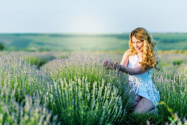 Gelukkig glimlachend blondemeisje in witte kleding op het lavendelgebied