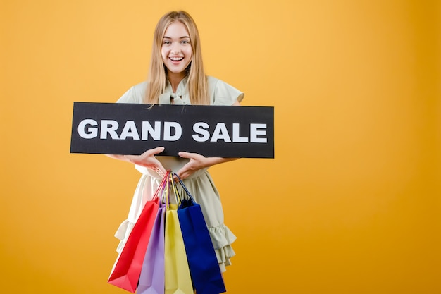 Gelukkig glimlachend blondemeisje met groot verkoopteken en kleurrijke die het winkelen zakken over geel wordt geïsoleerd