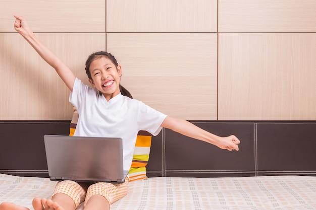 Gelukkig glimlachend en opgewekt aziatisch meisje die computerlaptop notitieboekje met behulp van