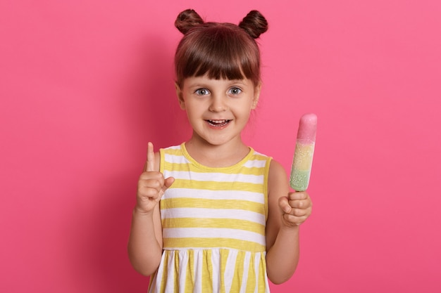 Gelukkig glimlachend jong geitje meisje met ijs en omhoog met haar wijsvinger, zomerjurk met witte en gele strepen dragen.