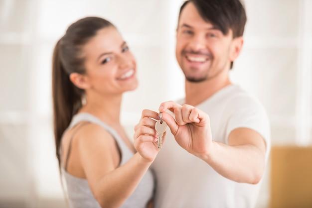 Gelukkig glimlachend jong paar dat sleutels van hun nieuw huis toont.