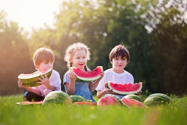 Gelukkig glimlachend kind drie die watermeloen in park eten.