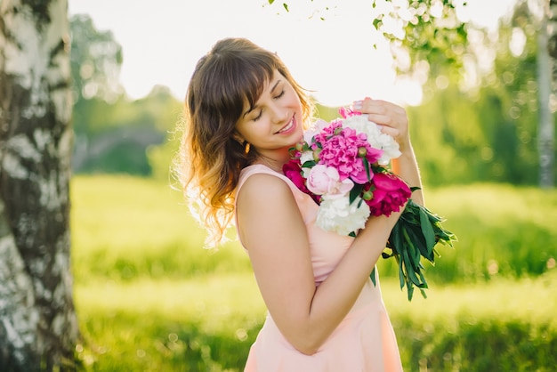 Gelukkig glimlachend meisje met bloemboeket in openlucht in de zomer