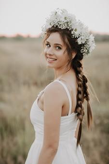 Gelukkig glimlachend meisje met vlechten en bloemenkroon in witte kleding in bohostijl in de zomer in openlucht