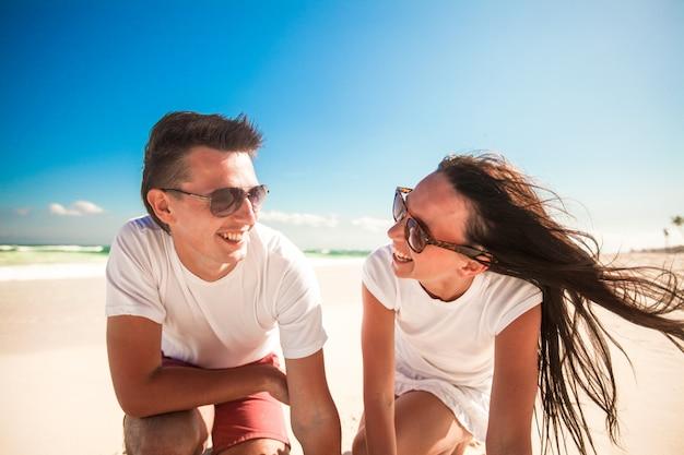 Gelukkig glimlachend paar op exotisch wit strand dat camera bekijkt