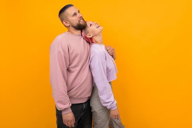 Gelukkig glimlachend paar van meisje en kerel met gekleurd haar in roze vrijetijdskleding en een doordringende tribune die zijdelings op een gele achtergrond omhelzen
