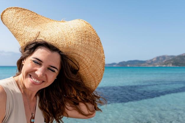 Gelukkig glimlachend vrouwenportret met gesloten ogen die een strohoed op het strand dragen met wind die haar ruches. prachtige doorschijnende zee op de achtergrond.