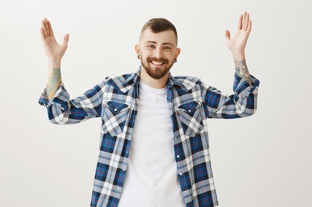 Gelukkig glimlachende man handen opsteken verheugd, goed nieuws ontvangen