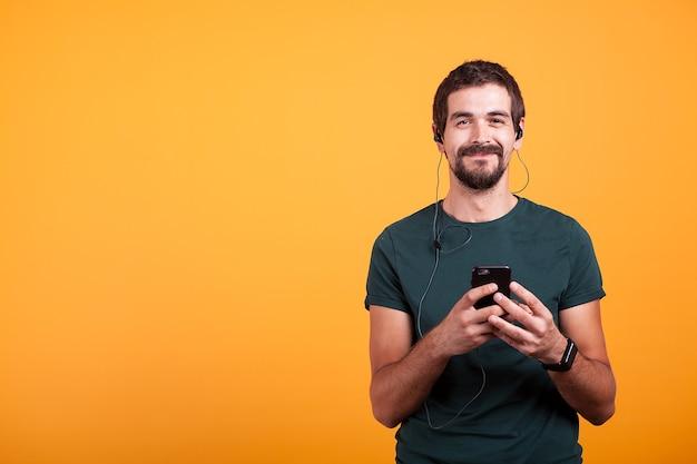 Gelukkig glimlachende man met koptelefoon op het luisteren van muziek op zijn smartphone geïsoleerd op gele achtergrond. mobiele entertainment levensstijl