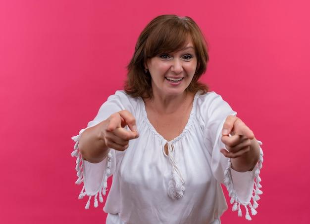 Gelukkig glimlachende vrouw van middelbare leeftijd die met vingers op geïsoleerde roze muur richt
