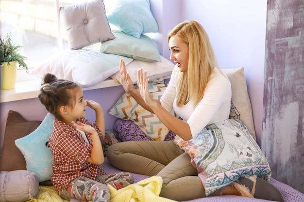 Gelukkig glimlachte moeder en dochter klappen samen handen in lichte kamer bij het raam, omringd met veel kussens