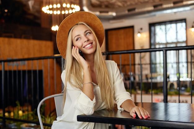 Gelukkig goed uitziende jonge langharige vrouw in wit overhemd en bruine hoed met aangenaam gesprek aan de telefoon zittend in restaurant tijdens de lunchpauze