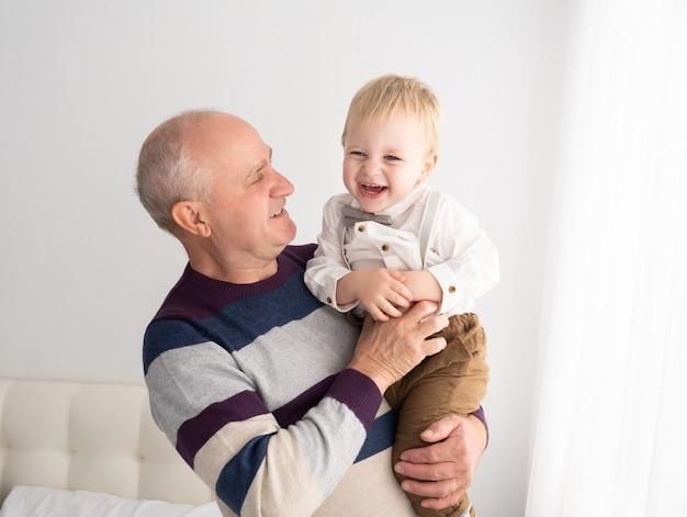 Gelukkig goed uitziende senior mannen met zijn schattige kleinzoon binnen
