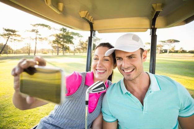 Gelukkig golfspelerpaar die zelfportret nemen