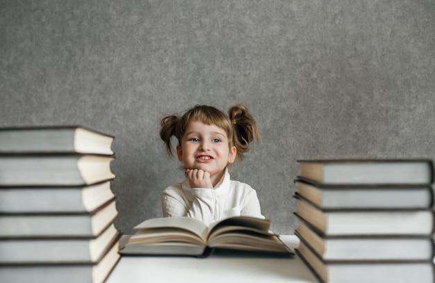 Gelukkig grappig babymeisje die in glazen een boek lezen