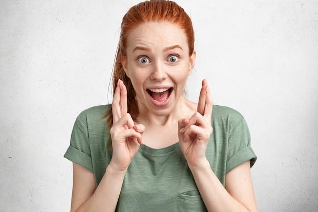 Gelukkig grappig dolblij gember vrouwtje met haar knoop, draagt casual t-shirt, kruist vingers met grote hoop, modellen in studio tegen wit