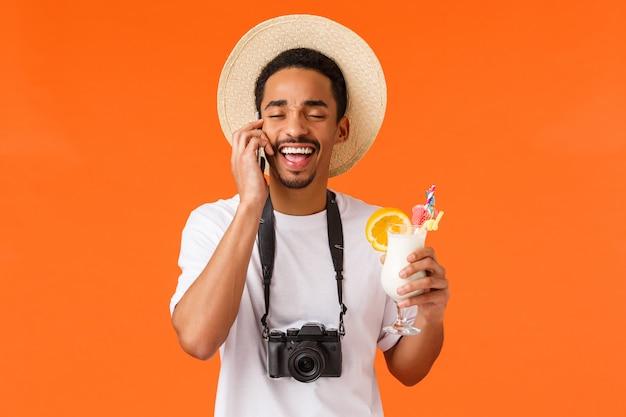 Gelukkig grappig en charismatisch, opgewonden afro-amerikaanse man in zomer hoed, camera