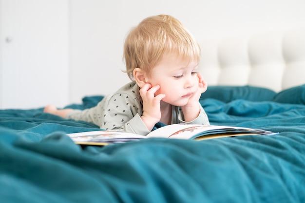 Gelukkig grappig jongetje in pyjama's lezen boek liggend in het bed van zijn ouders.