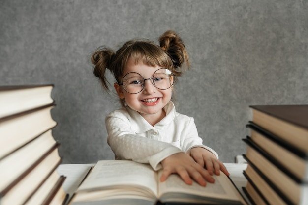 Gelukkig grappig kaukasisch babymeisje die in glazen een boek lezen. emotioneel meisje. binnenkort naar school.